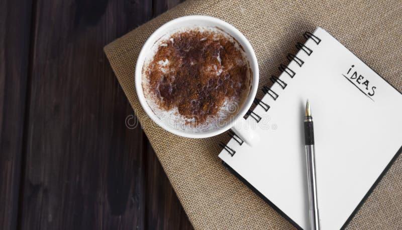 笔记本有在一份可口咖啡附近的想法 库存照片