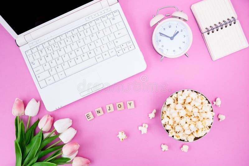 笔记本笔记薄郁金香玉米花闹钟花束在一个碗的在桌面上 免版税库存照片