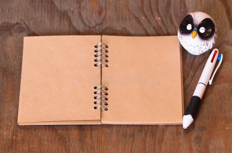 笔记本纸和笔和玩偶wol 免版税库存图片