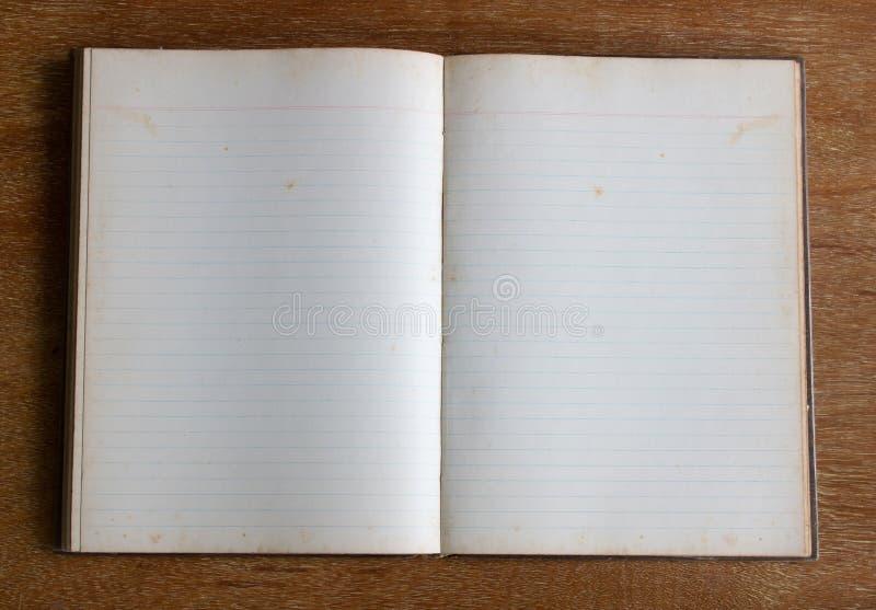 笔记本老空白页在木桌上的 免版税库存图片