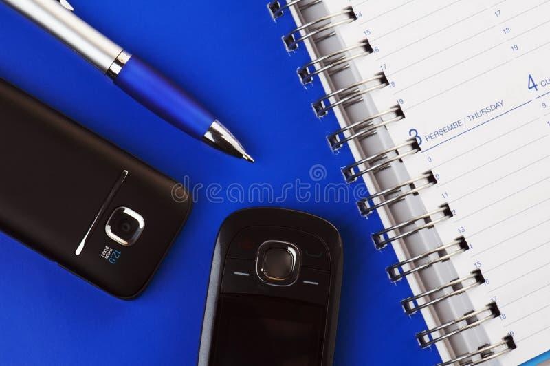 笔记本被开张的铅笔电话 免版税图库摄影