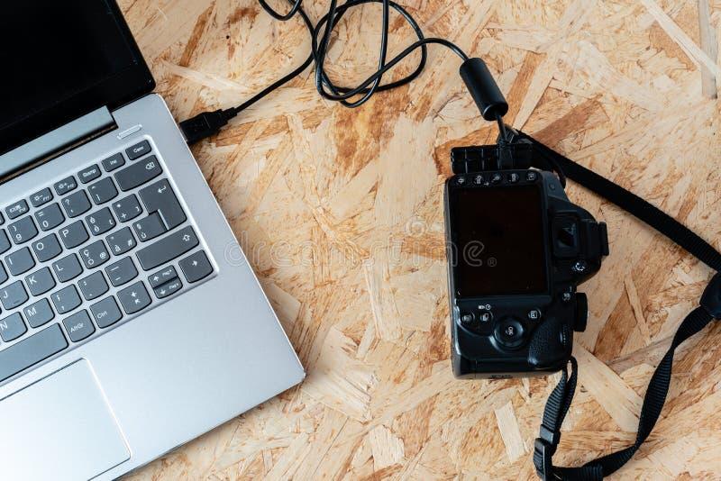 笔记本被连接到一台数字SLR照相机用usb缆绳,thetering的方式 图库摄影