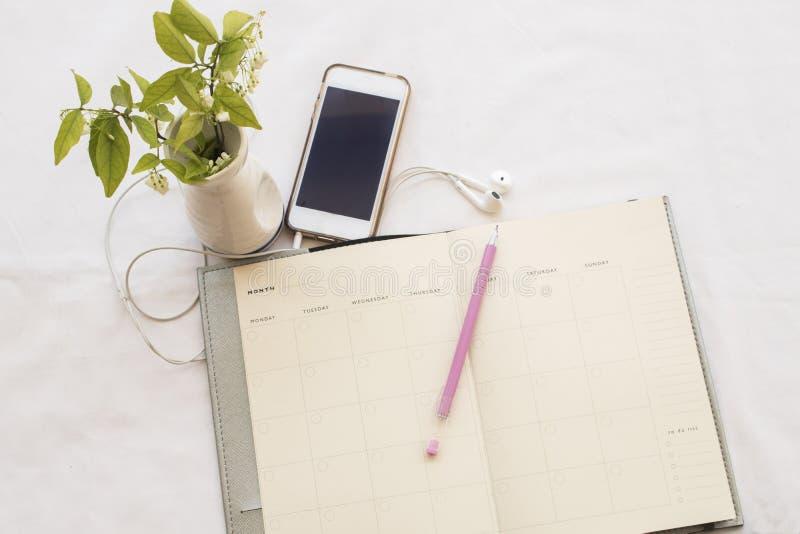 笔记本计划者和机动性在白色 免版税库存照片