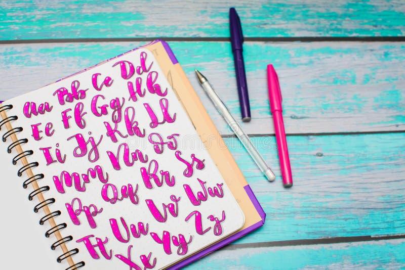 笔记本顶视图有手拉的abc字母表信件和五颜六色的笔的在蓝色木书桌背景 免版税库存照片