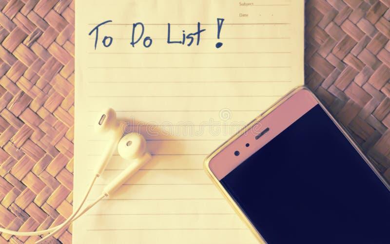 笔记本,与要做在棕色葡萄酒过滤器e的名单的手机 库存图片