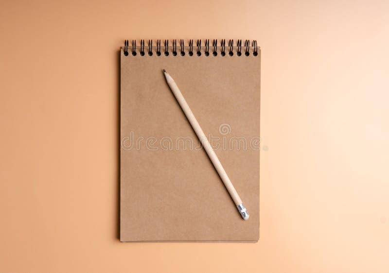 笔记本,在颜色橙色背景的铅笔 免版税库存图片