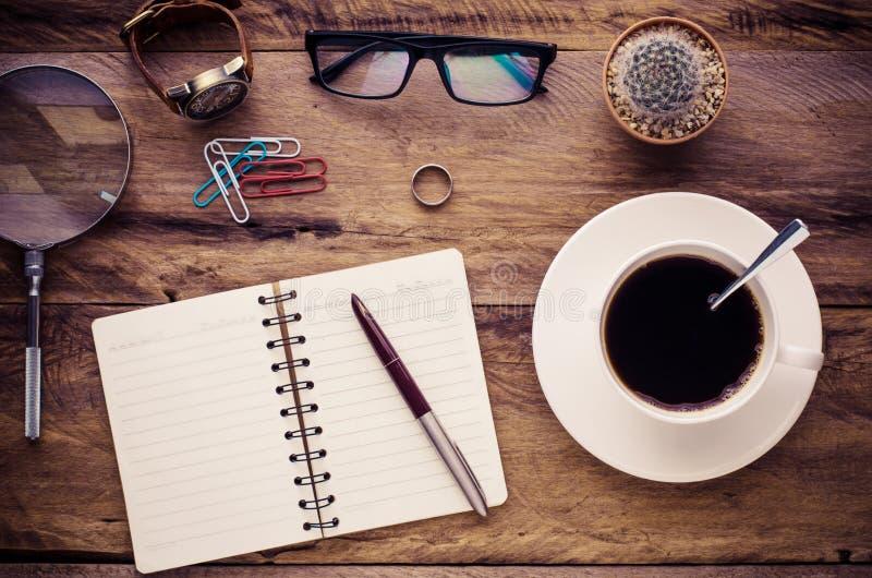 笔记本,杯子,在一张木书桌上的玻璃 免版税库存照片