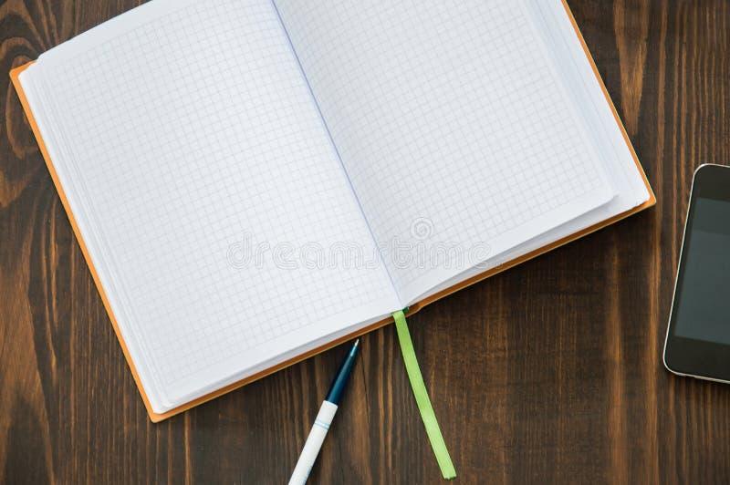 笔记本,电话,笔在地板放置 免版税库存照片