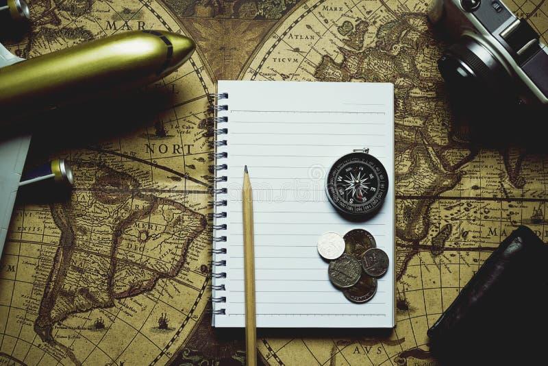 笔记本,铅笔,照相机,指南针,硬币,钱包,在迷离葡萄酒世界地图,旅途概念,拷贝空间,减速火箭的口气的飞机 免版税库存照片