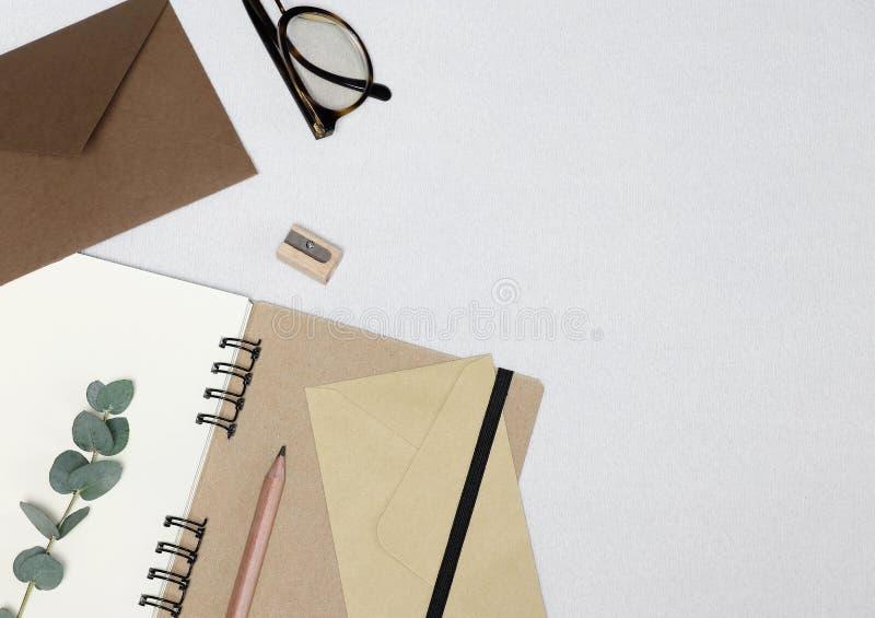 笔记本,铅笔,磨削器,眼镜,信封,在白色背景的玉树分支 库存图片