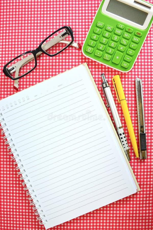 笔记本,黄色笔,灰色铅笔,绿色计算器,切削刀刀子 免版税库存照片