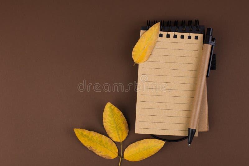 笔记的一个开放笔记本关于棕色背景 文本的空位 秋天大气和黄色叶子 顶视图 平的位置 图库摄影