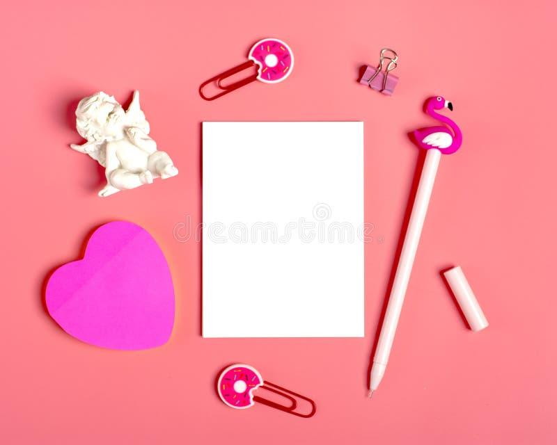 笔记的白色板料,纸夹,笔-火鸟,sukulent家庭的花,贴纸-心脏,姜饼,天使小雕象,桃红色backg 库存图片