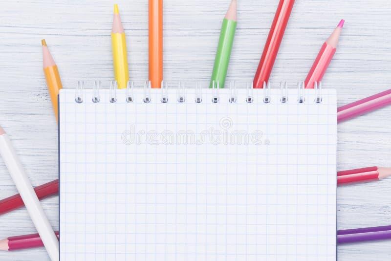 笔记的白色笔记本在色的铅笔,题字的背景说谎 免版税图库摄影