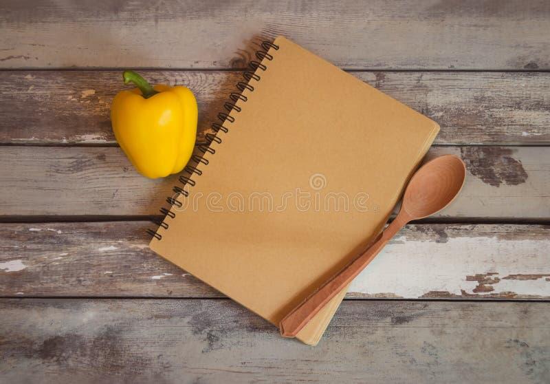 笔记的被打开的笔记本和在年迈的木背景的黄色甜椒 免版税库存照片