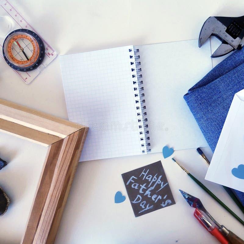 笔记薄、指南针、板钳、生` s天的框架在牛仔布和明信片 免版税图库摄影
