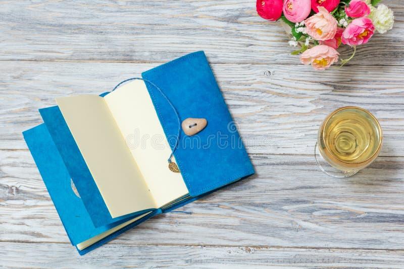 笔记薄、白葡萄酒和花 免版税图库摄影