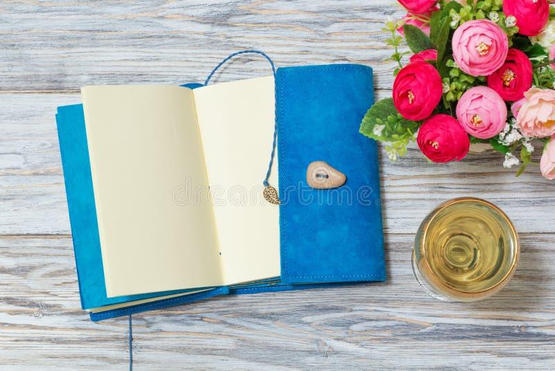 笔记薄、白葡萄酒和花 库存照片