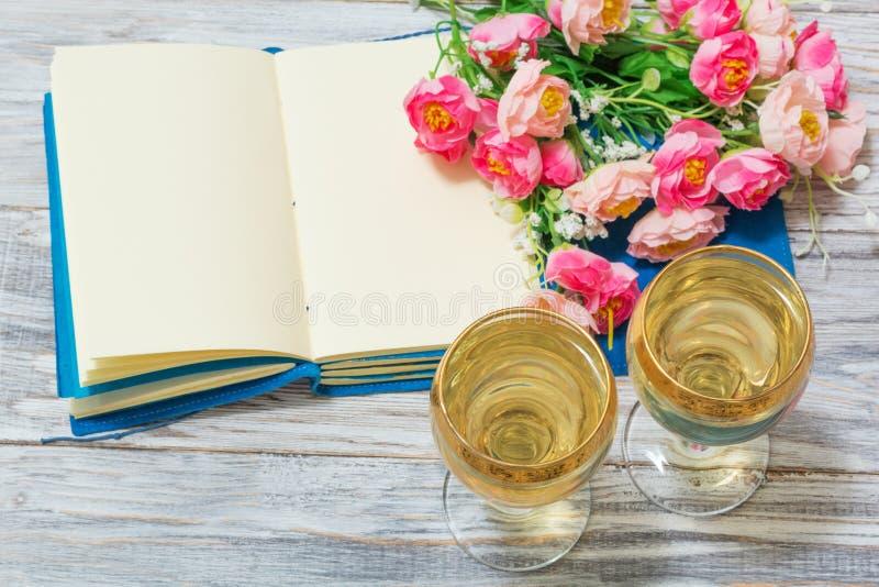 笔记薄、白葡萄酒和花 免版税库存图片