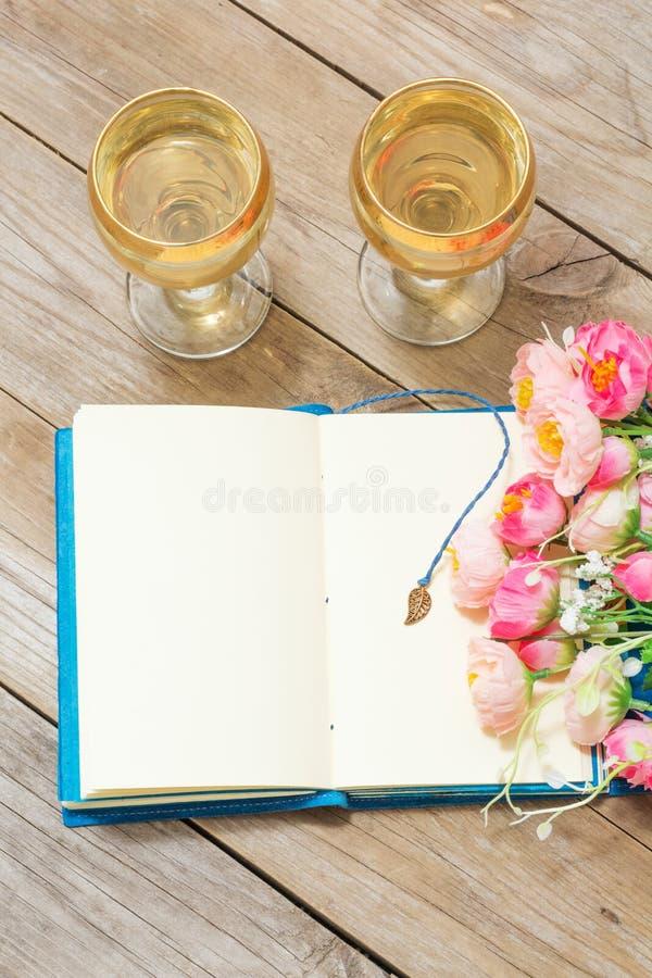 笔记薄、白葡萄酒和花 库存图片