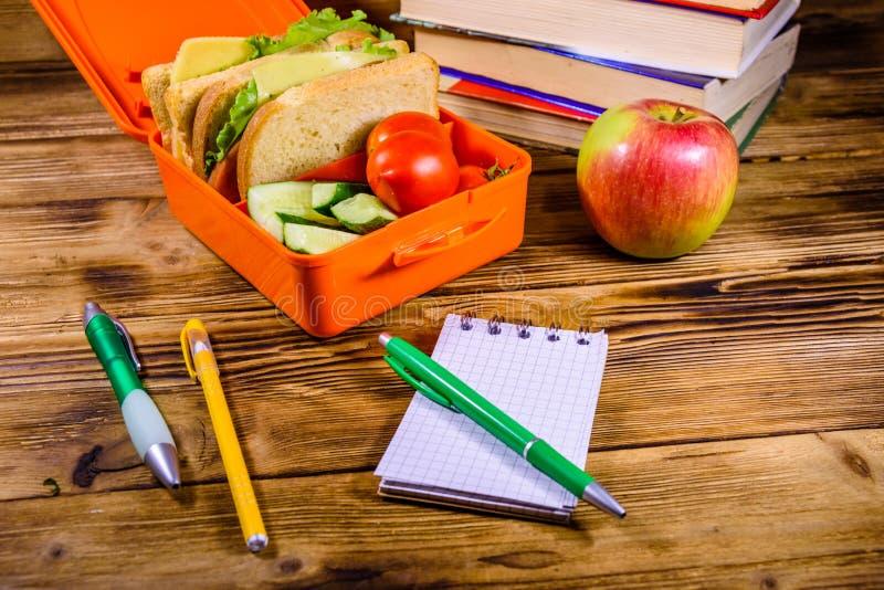 笔记薄、笔、成熟苹果、堆书和饭盒用三明治、黄瓜和蕃茄在木桌上 库存照片
