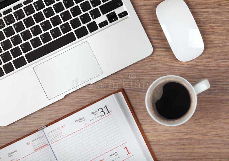 笔记薄、膝上型计算机和咖啡杯在木桌上 图库摄影