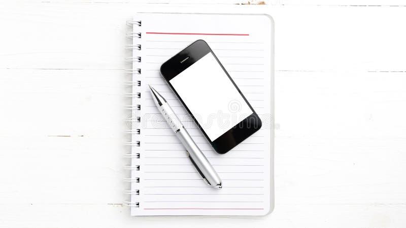 笔记薄和手机 库存照片