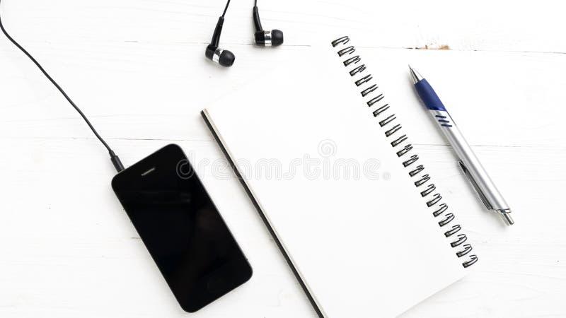 笔记薄和手机 库存图片