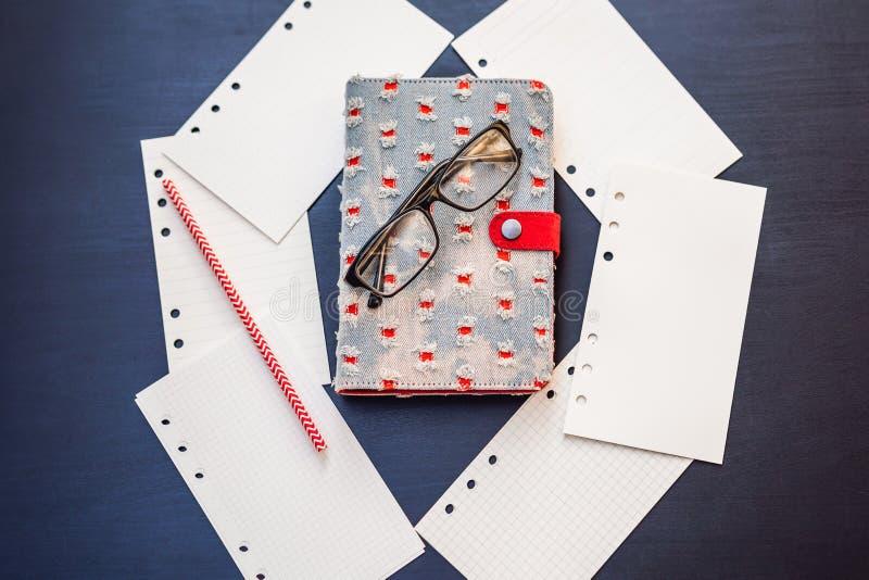 笔记薄和文具在黑背景 事务和研究的计划者 文具爱好者  免版税库存图片