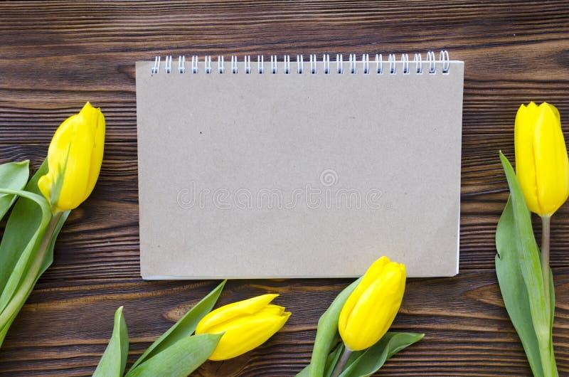 笔记薄和黄色郁金香在木桌上 文本的空间 库存照片