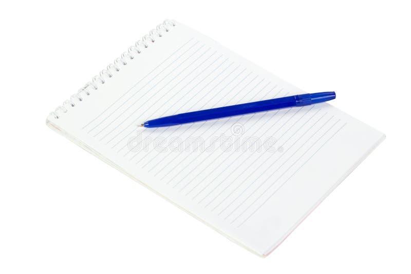 笔记薄和说谎在白色隔绝的一支蓝色笔 库存照片