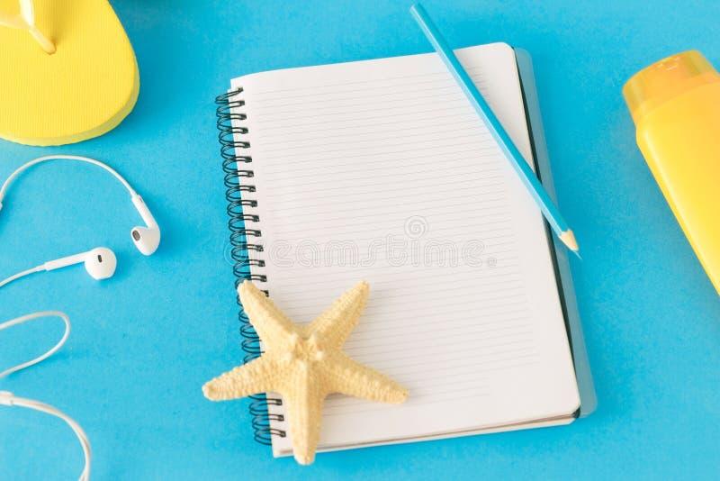 笔记薄铅笔在蓝色背景的海滩辅助部件 免版税库存图片