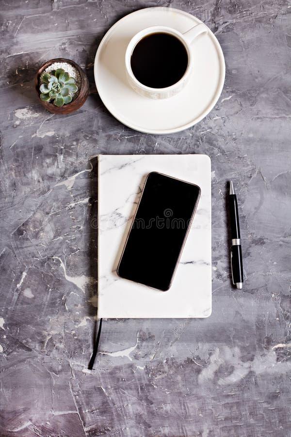 笔记薄,手机,笔,多汁植物,玻璃,咖啡在灰色水泥背景的 免版税库存图片