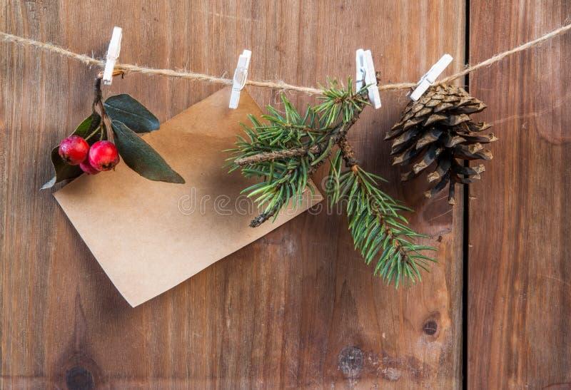 笔记,圣诞树分支、杉木锥体和冬天莓果在一条绳索与晒衣夹 免版税图库摄影