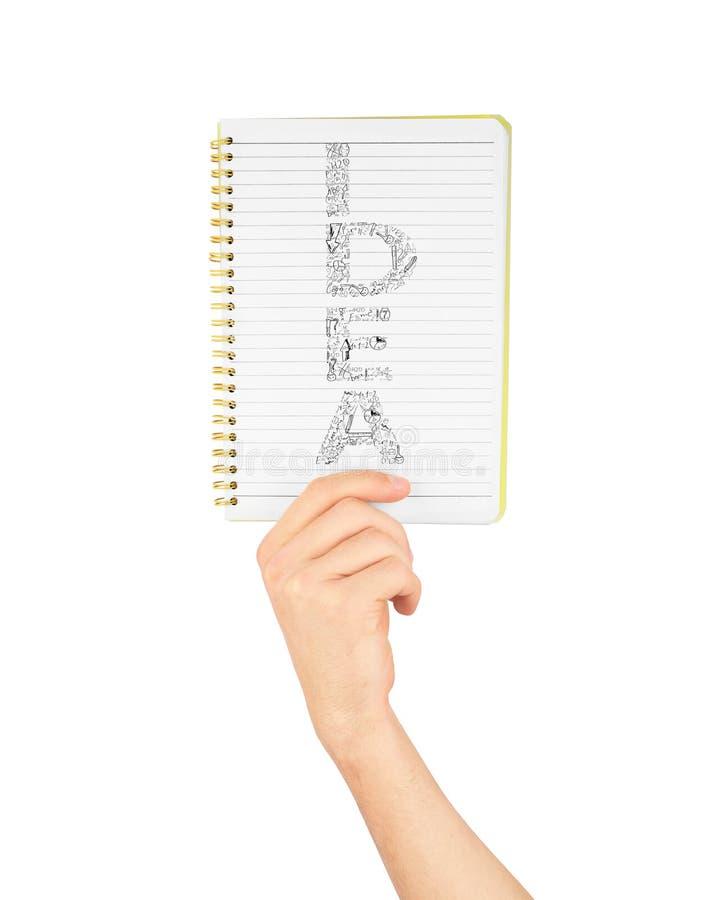 笔记,拿着笔记本的手 库存照片