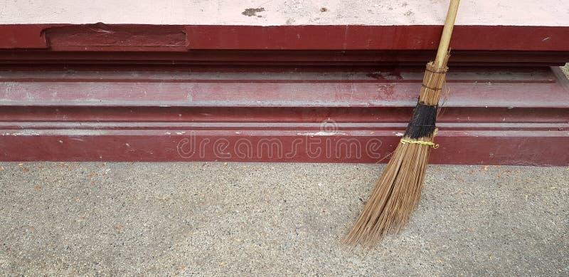 笤帚对干净的尘土的红色墙壁和清扫垃圾 库存照片