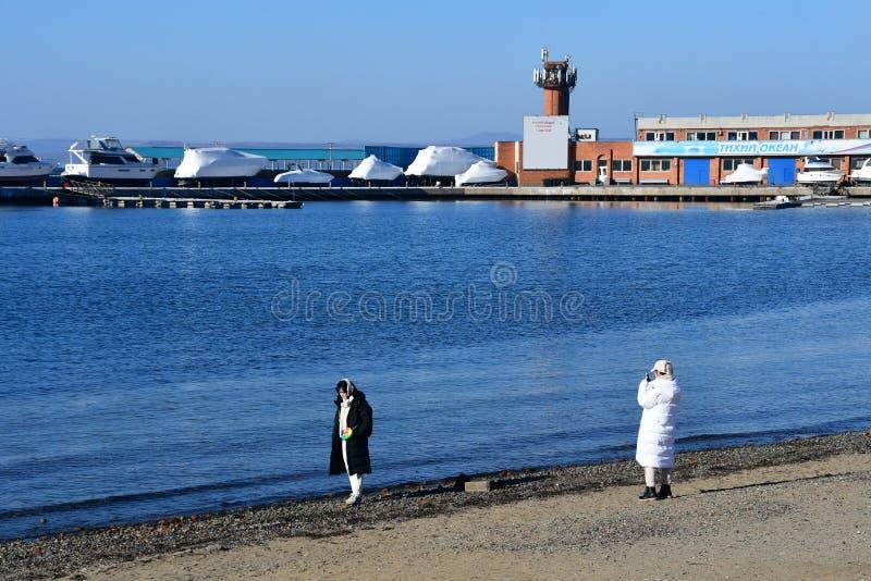 符拉迪沃斯托克,俄罗斯,2018年12月,24日 符拉迪沃斯托克中央海滩的韩国游人在冬天 不典型操作的1月 免版税库存图片
