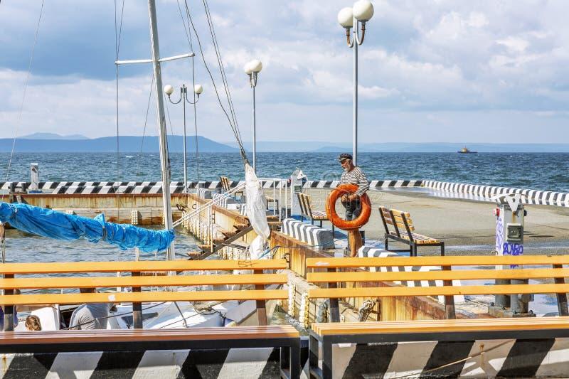 符拉迪沃斯托克,俄罗斯,09/20/2017:码头的一个年长上尉在小游艇船坞准备一条小船 在晴朗的美好的海景 免版税库存照片
