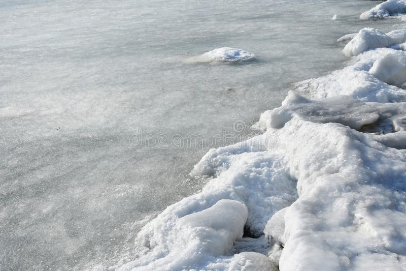 符拉迪沃斯托克,Patrokl海湾在冬天 冰川覆盖的海滩和小烂泥的边界在水中 图库摄影