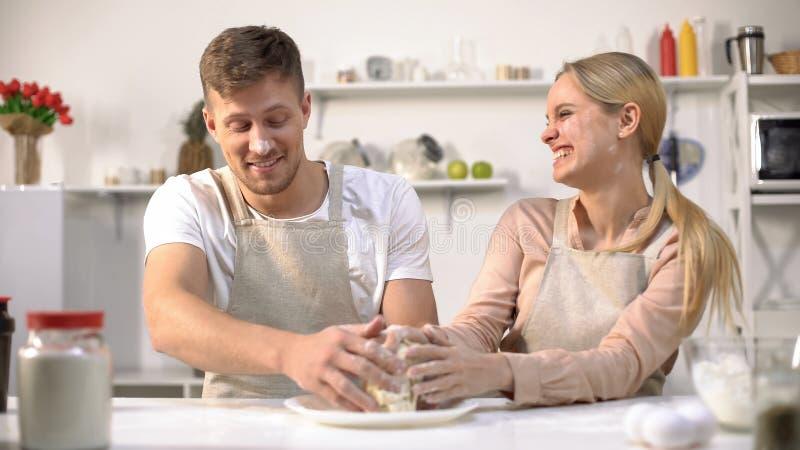 笨拙地揉面团的愉快的夫妇,一起花费乐趣时间在厨房里 库存照片