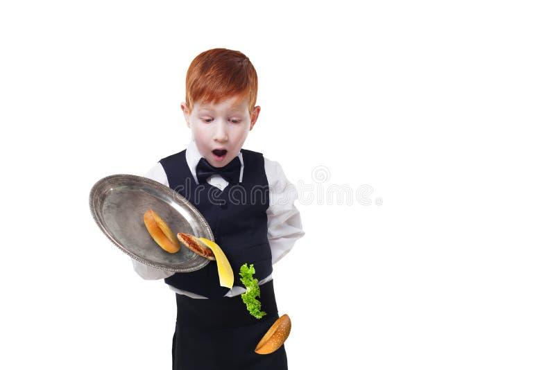 笨拙的矮小的侍者从盘子投下食物,当供食汉堡包时 免版税图库摄影
