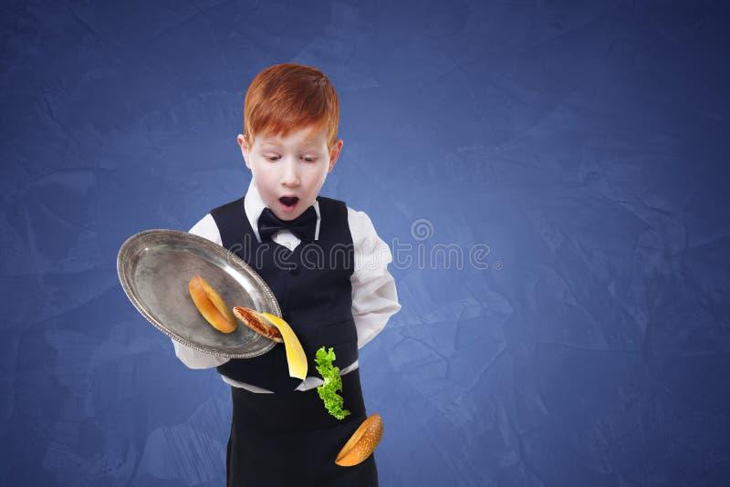 笨拙的矮小的侍者从盘子投下食物,当供食汉堡包时 免版税库存图片