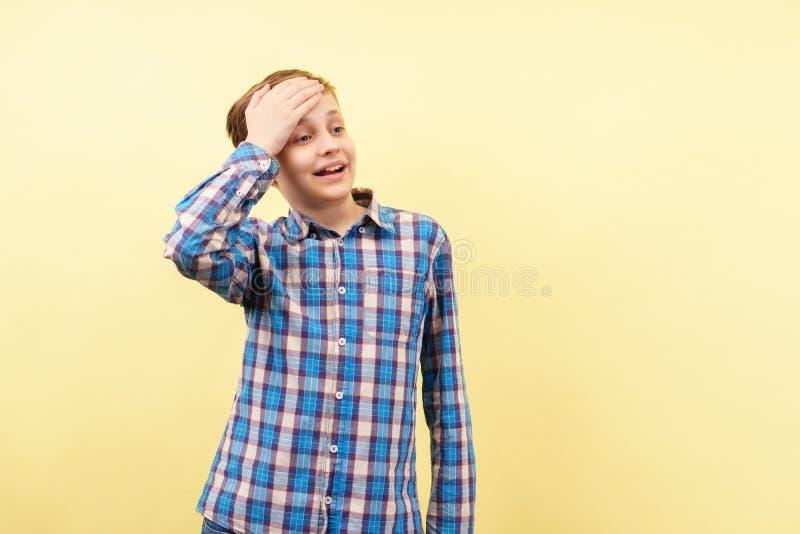 笨拙窘迫男孩用手盖前额 库存图片