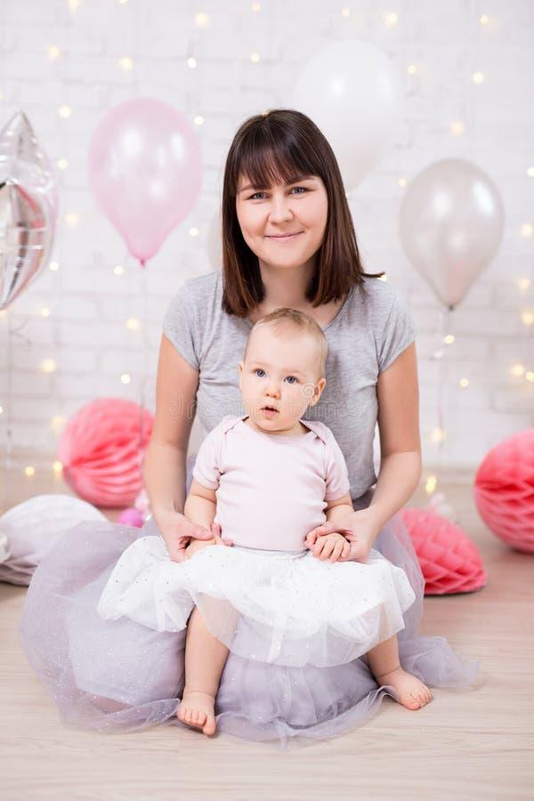 第一个生日概念-有母亲的可爱宝贝女孩在装饰的屋子里 免版税库存照片