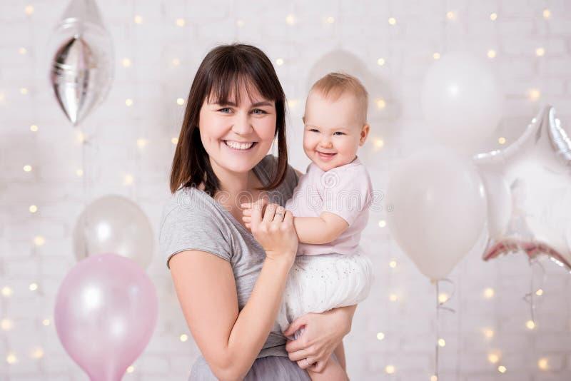 第一个生日概念-母亲画象有可爱宝贝女孩的在气球 免版税库存图片