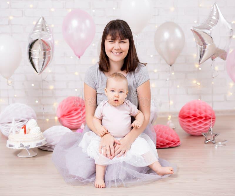 第一个生日-有母亲的美女在有蛋糕和气球的装饰的屋子里在白色墙壁 库存照片