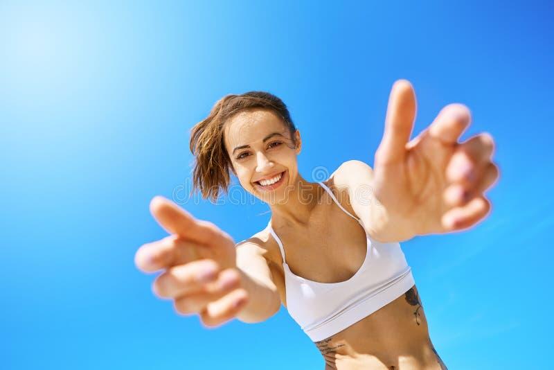 第一人观点的美丽的愉快的微笑的妇女用对照相机的被伸出的手在天空蔚蓝背景 ?? 免版税库存照片