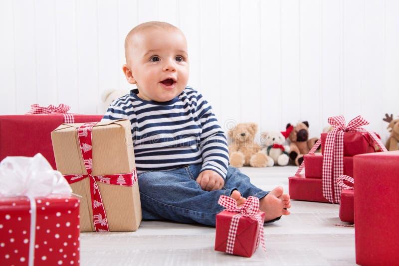 第一圣诞节:在红色礼物中的婴孩和微笑着 免版税图库摄影
