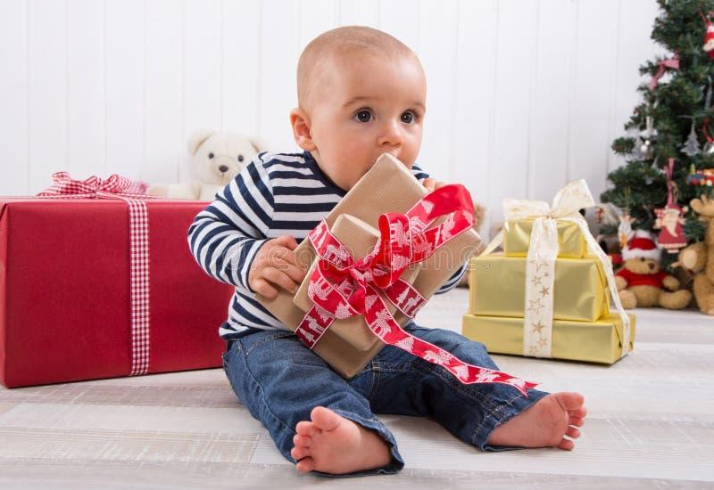 第一圣诞节:解开一个红色礼物-逗人喜爱的l的赤足婴孩 免版税库存照片