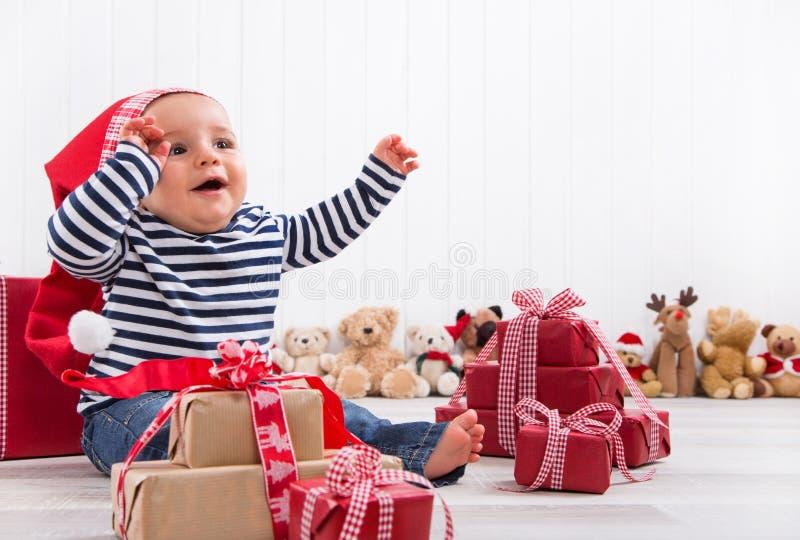 第一圣诞节:解开礼物的婴孩-愉快的孩子注视 免版税图库摄影